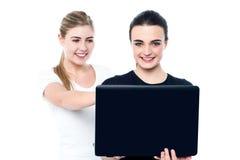 Jonge mooie meisjes die op films op laptop letten Stock Afbeeldingen