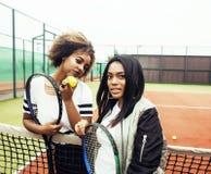 Jonge mooie meisjes die op tennisbaan, manierstylis hangen Stock Foto's
