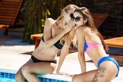 Jonge mooie meisjes die, roddelen, die dichtbij zwembad ontspannen glimlachen Stock Afbeeldingen