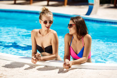 Jonge mooie meisjes die, spreken, die in zwembad ontspannen glimlachen Royalty-vrije Stock Fotografie