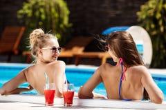 Jonge mooie meisjes die, spreken, die in zwembad ontspannen glimlachen Stock Afbeeldingen