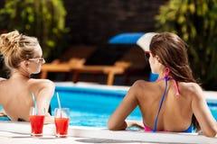 Jonge mooie meisjes die, spreken, die in zwembad ontspannen glimlachen Stock Afbeelding
