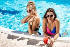 Jonge mooie meisjes die, spreken, die in zwembad ontspannen glimlachen Royalty-vrije Stock Afbeelding