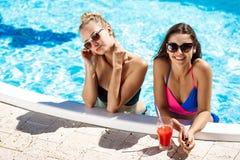 Jonge mooie meisjes die, spreken, die in zwembad ontspannen glimlachen Royalty-vrije Stock Foto's
