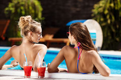 Jonge mooie meisjes die, spreken, die in zwembad ontspannen glimlachen Stock Fotografie