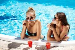 Jonge mooie meisjes die, voor de gek houden, het spreken, die in zwembad ontspannen glimlachen Stock Afbeelding