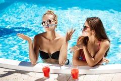 Jonge mooie meisjes die, voor de gek houden, het spreken, die in zwembad ontspannen glimlachen Royalty-vrije Stock Afbeeldingen