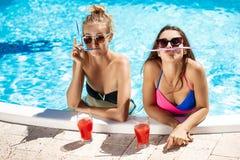 Jonge mooie meisjes die, voor de gek houden, het spreken, die in zwembad ontspannen glimlachen Royalty-vrije Stock Foto's