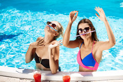 Jonge mooie meisjes die, voor de gek houden, het spreken, die in zwembad ontspannen glimlachen Royalty-vrije Stock Fotografie