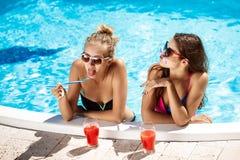Jonge mooie meisjes die, voor de gek houden, het spreken, die in zwembad ontspannen glimlachen Royalty-vrije Stock Afbeelding