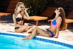 Jonge mooie meisjes die, zonnebaden, die dichtbij zwembad ontspannen glimlachen Royalty-vrije Stock Afbeeldingen