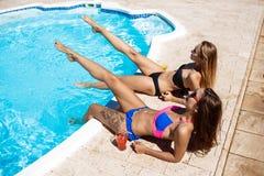 Jonge mooie meisjes die, zonnebaden, die dichtbij zwembad ontspannen glimlachen Royalty-vrije Stock Foto's