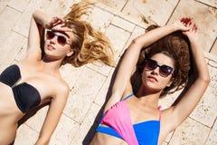 Jonge mooie meisjes die, zonnebaden, die dichtbij zwembad ontspannen glimlachen Stock Foto's