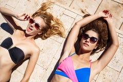 Jonge mooie meisjes die, zonnebaden, die dichtbij zwembad ontspannen glimlachen Royalty-vrije Stock Foto