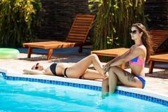 Jonge mooie meisjes die, zonnebaden, die dichtbij zwembad ontspannen glimlachen Stock Foto