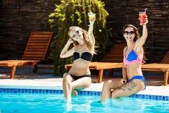 Jonge mooie meisjes die, zonnebaden, die dichtbij zwembad ontspannen glimlachen Royalty-vrije Stock Afbeelding