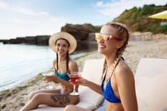 Jonge mooie meisjes die, zonnebaden, die op chaises dichtbij overzees liggen glimlachen Stock Fotografie