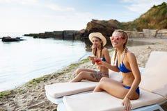 Jonge mooie meisjes die, zonnebaden, die op chaises dichtbij overzees liggen glimlachen Royalty-vrije Stock Foto's