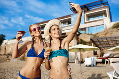 Jonge mooie meisjes in het swimwear glimlachen, die selfie bij strand maken Stock Afbeelding