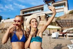Jonge mooie meisjes in het swimwear glimlachen, die selfie bij strand maken Stock Foto's