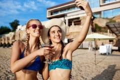 Jonge mooie meisjes in het swimwear glimlachen, die selfie bij strand maken Royalty-vrije Stock Fotografie