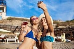 Jonge mooie meisjes in het swimwear glimlachen, die selfie bij strand maken Stock Foto