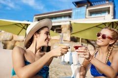 Jonge mooie meisjes in het swimwear glimlachen, het drinken sap bij kust Royalty-vrije Stock Afbeeldingen