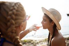 Jonge mooie meisjes in swimwear het drinken sap op zee strand Royalty-vrije Stock Foto's