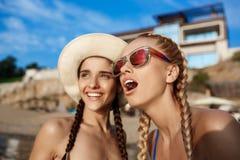 Jonge mooie meisjes in zich het swimwear verheugen, het glimlachen, die bij kust lachen Royalty-vrije Stock Foto's