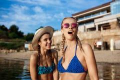 Jonge mooie meisjes in zich het swimwear verheugen, het glimlachen, die bij kust lachen Royalty-vrije Stock Afbeeldingen