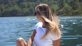 Jonge mooie meisjeszitting op dek van boot en het kijken aan mooie aard op zonnige dag Gelukkige vrouw met blondehaar stock video