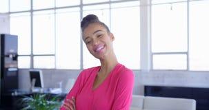 Jonge mooie mengen-ras vrouwelijke uitvoerende die status met wapens in modern bureau 4k worden gekruist stock video