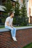 Jonge mooie modieuze mens die met varkenshaar op een baksteenomheining dichtbij het gebouw op een de zomeravond zitten royalty-vrije stock foto's