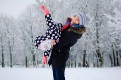 Jonge mooie moeder die buiten met haar weinig dochter in het sneeuwpark spelen tijdens een dag Actieve grappige mammaholding Stock Afbeeldingen
