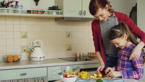 Jonge mooie moeder die haar leuke dochter onderwijzen om groenten behoorlijk te snijden Meisje het koken samen met het houden van stock videobeelden