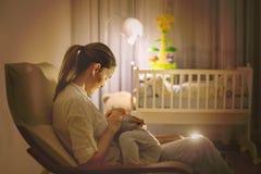 Jonge mooie moeder, die haar pasgeboren babyjongen de borst geven bij Ni stock fotografie