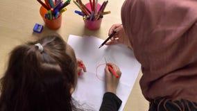 Jonge mooie moeder in hijab, kleine dochterverven met kleurpotloden, verven, kinderen` s kleuring, familieidylle stock video