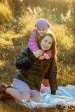 Jonge mooie moeder met haar dochter op een gang op een zonnige de herfstdag Zij zitten op een plaid op het gras dicht bij elkaar, stock fotografie