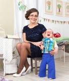 Jonge mooie moeder met weinig lachende zoon thuis Stock Afbeeldingen