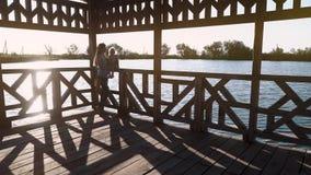 Jonge mooie moederzitting in een houten structuur tegen de zonsondergang, dichtbij het meer stock video