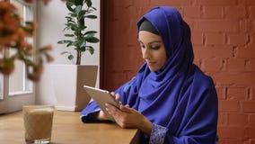 Jonge mooie moslimvrouw in blauwe hijab gebruikend tablet en zittend in koffie, charmant wijfje met doordrongen neus stock footage