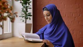Jonge mooie moslimvrouw in het blauwe boek van de hijablezing in koffie en het glimlachen bij camera, charmant wijfje met doordro stock video