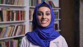 Jonge mooie moslimvrouw in hijab die zich in bibliotheek bevinden en bij camera met gelukkige uitdrukking glimlachen stock footage