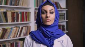 Jonge mooie moslimvrouw in hijab die zich in bibliotheek bevinden en camera met ernstige uitdrukking bekijken stock footage