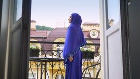 Jonge mooie moslimvrouw in naar balkon gaan en hijab die, profiel van het charmeren van dame zich daar bevinden stock footage