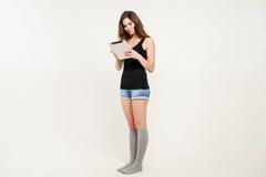 Jonge mooie onderneemster die digitale tablet in haar handen houden terwijl status geïsoleerd op wit Royalty-vrije Stock Fotografie