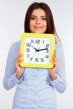 Jonge mooie onderneemster die een klok houden Stock Afbeelding