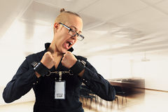 Jonge mooie onderneemster die met woede in bureau, gevangene gilt van baan in manchetten Stock Afbeeldingen