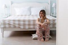 Jonge mooie ongelukkige vrouwenzitting in slaapkamer royalty-vrije stock foto