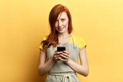Jonge mooie roodharige tuinman met schort die een bericht met mobiel verzenden stock foto's